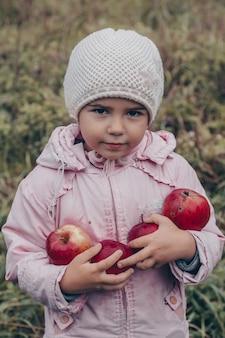 Bambino felice che tiene le mele rosse nelle sue mani. harvest funny kid all'aperto nella sosta di autunno.