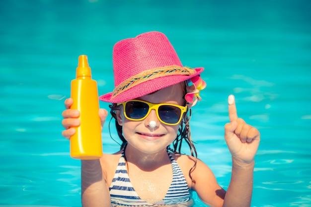 Bambino felice che tiene in mano una crema solare. concetto di vacanze estive