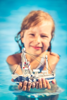 Bambino felice che tiene in mano la barca a vela giocattolo bambino che gioca in piscina vacanze estive e concetto di viaggio