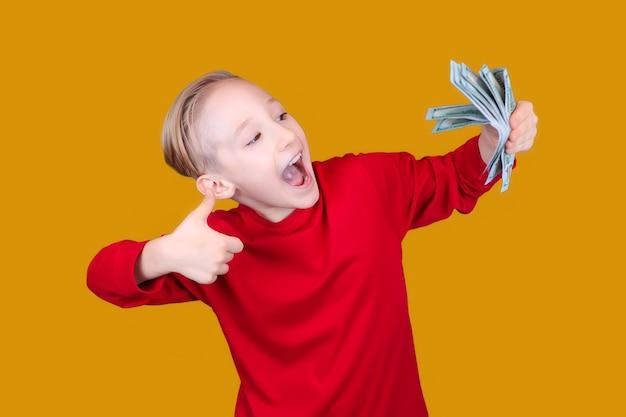 Il bambino felice tiene le banconote in mano e dà il pollice in su