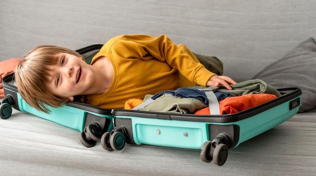 Bambino felice a casa con i bagagli per viaggiare