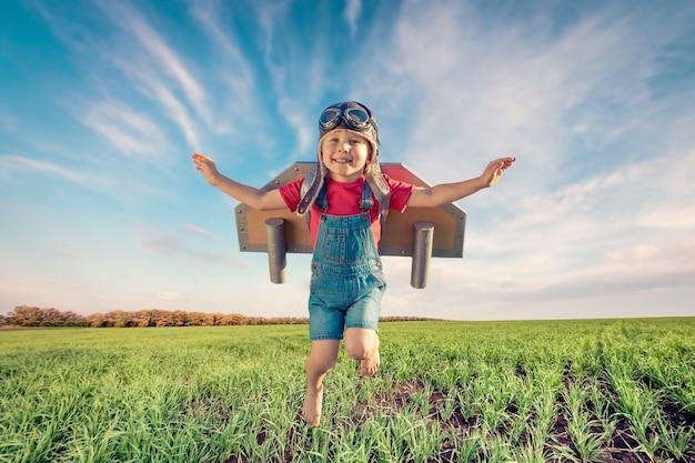Bambino felice che salta contro il cielo blu.
