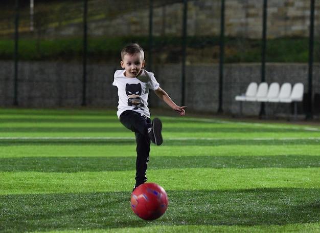 Bambino felice calcia una palla rossa sul campo di calcio, di notte