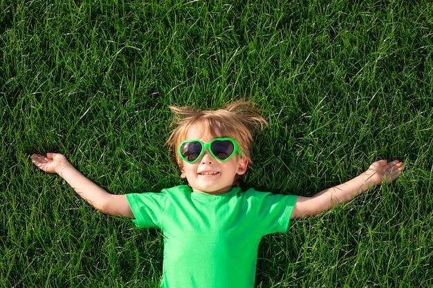 Bambino felice che pone sull'erba verde