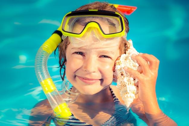 Il bambino felice ascolta la conchiglia in spiaggia concetto di vacanze estive