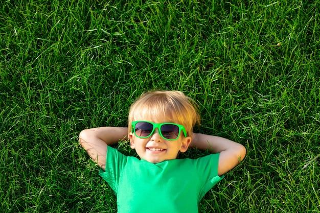 Bambino felice sdraiato sull'erba verde.