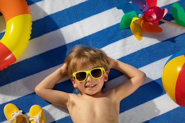 Bambino felice che si trova sul tovagliolo a strisce all'aperto