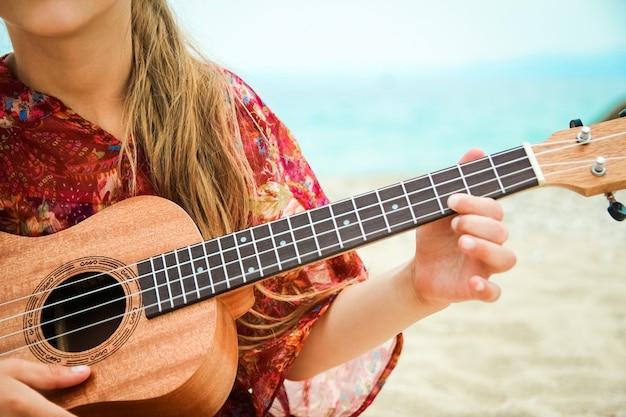 Bambino felice che gioca chitarra in riva al mare in grecia sulla natura
