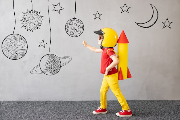 Bambino felice che gioca. capretto con razzo di carta giocattolo. ritratto del bambino contro il fondo grigio del muro di cemento. concetto di sogno creativo, immaginazione e bambini