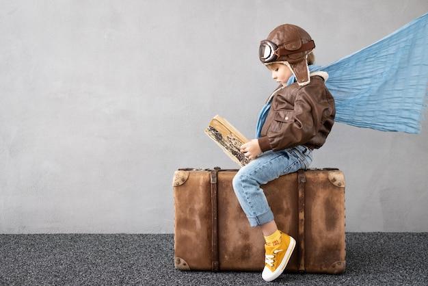 Bambino felice che gioca all'aperto. bambino sorridente che sogna di vacanze estive e viaggi. immaginazione e concetto di libertà