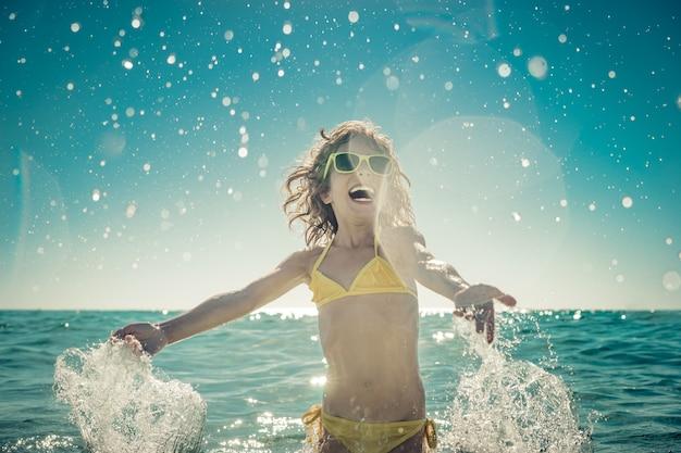 Bambino felice che gioca nel mare