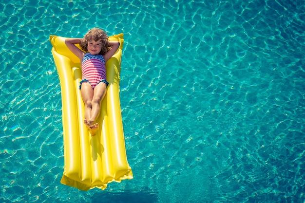 Bambino felice che gioca in piscina ritratto vista dall'alto