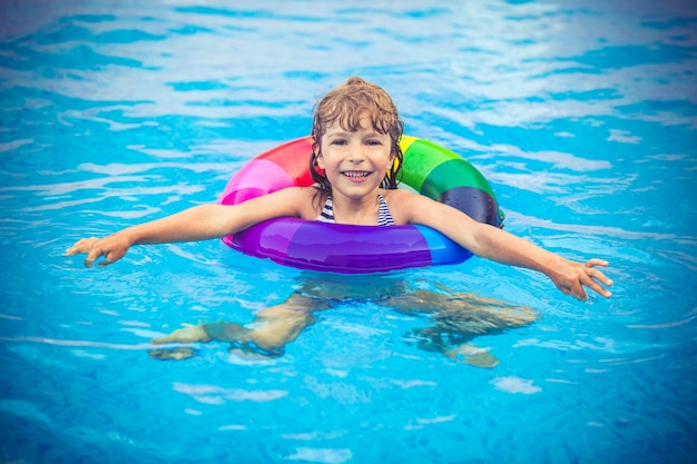 Bambino felice che gioca in piscina.