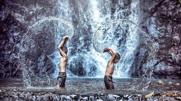 Bambino felice che gioca alla cascata. kid divertirsi all'aria aperta.