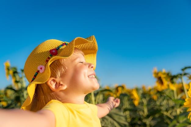 Bambino felice che gioca con il girasole all'aperto. kid divertirsi nel campo di primavera verde su sfondo blu cielo.