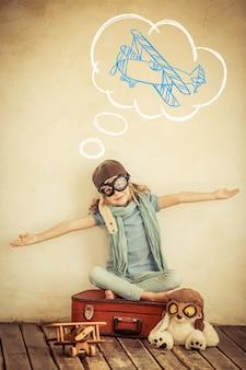 Bambino felice che gioca con l'aeroplano giocattolo a casa. dai toni retrò