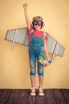 Bambino felice che gioca con il jetpack giocattolo a casa. successo e concetto di leader