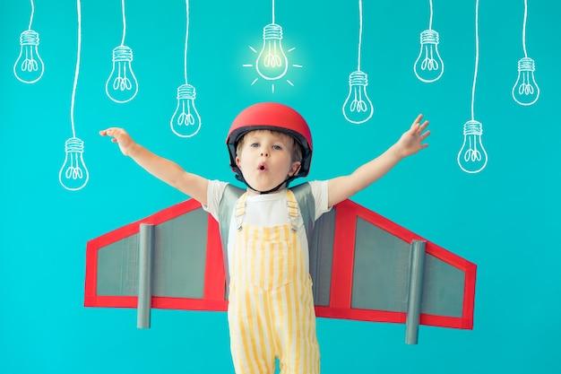 Bambino felice che gioca con le ali di carta giocattolo contro il muro blu a casa.