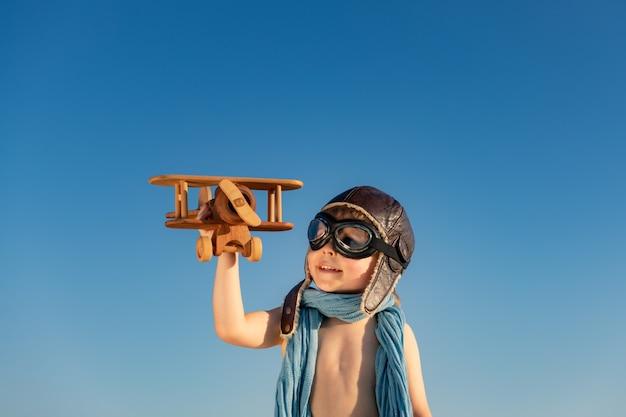 Bambino felice che gioca con l'aeroplano di legno dell'annata. kid divertirsi all'aperto sullo sfondo del cielo estivo