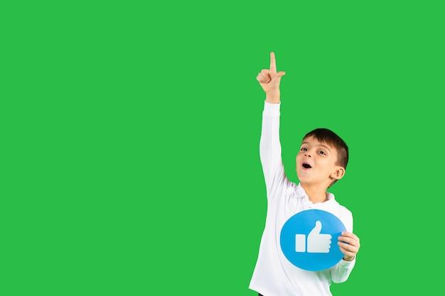 Il bambino felice indica con il dito indice che tiene un segno simile