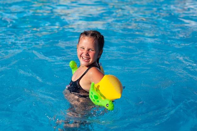 Bambino felice posa in piscina bambina sorridente in bracciali gonfiabili con dinosauri impara a nuotare in p...