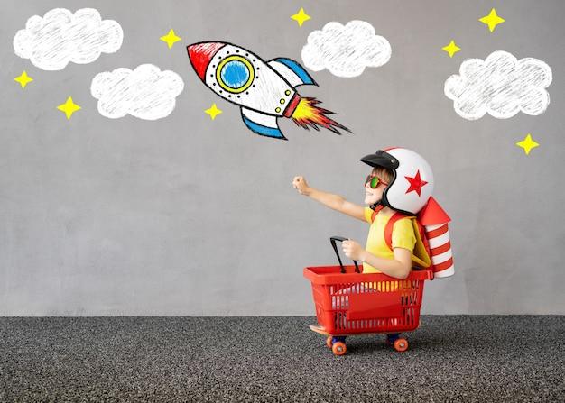 Il bambino felice finge di essere astronauta. bambino che gioca all'aperto. concetto di immaginazione creativa e per bambini