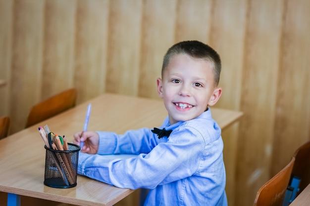 Un bambino felice al banco di scuola a scuola dopo la scuola
