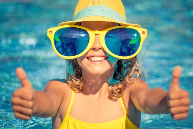 Bambino felice che mostra i pollici in su in piscina. ragazza che si diverte in vacanza estiva