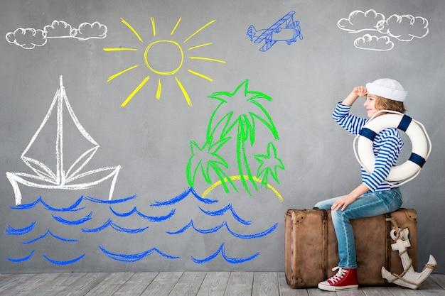 Bambino felice seduto su una vecchia valigia vestito come un capitano con cartoni animati su sfondo grigio