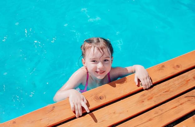 Un bambino felice in costume da bagno sta nuotando in piscina e si tiene a lato