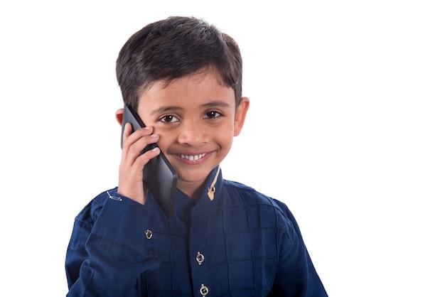 Bambino felice utilizzando il telefono cellulare su sfondo bianco.