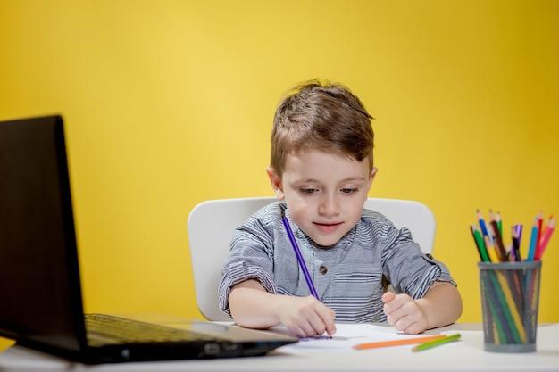 Bambino felice che per mezzo del computer portatile digitale che fa i compiti su sfondo giallo. distanziamento sociale, formazione online in e-learning.