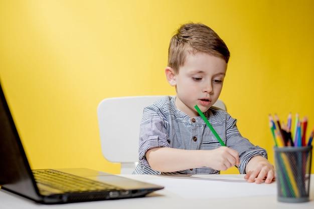 Bambino felice che per mezzo del computer portatile digitale che fa i compiti su priorità bassa gialla. distanziamento sociale, formazione online in e-learning.