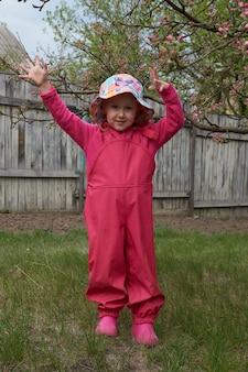 Bambino felice in cappotto impermeabile e stivali di gomma gode all'aperto. una ragazza si diverte sotto la pioggia con un impermeabile luminoso in campagna. albero del fiore del fiore di primavera.