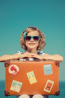 Bambino felice con occhiali da sole blu e una valigia vintage con adesivi