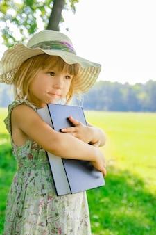 Un bambino felice con un libro sulla natura della bibbia nel parco
