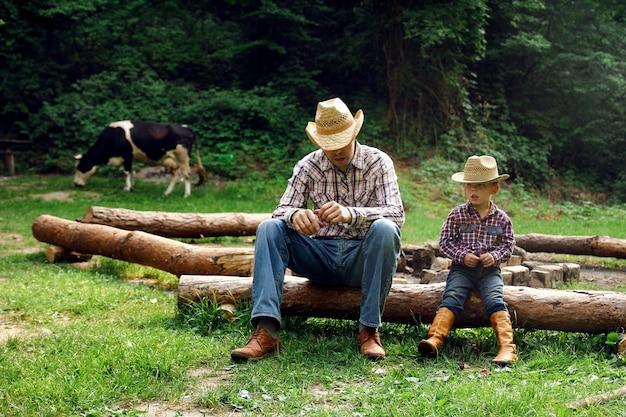 Bambino felice con un genitore cowboy in natura nel campo con mucca