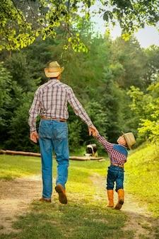 Bambino felice con il genitore del cowboy in natura nel campo