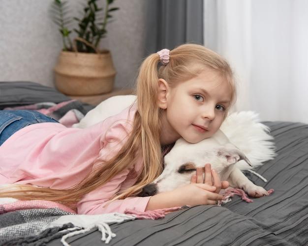 Bambino felice con il cane. ragazza del ritratto con l'animale domestico. ragazza e jack russell bianco