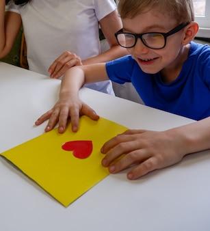 Un bambino felice con gli occhiali ha realizzato un biglietto con le sue stesse mani per la festa del papà di san valentino