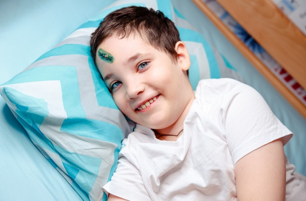 Un bambino felice con una cicatrice sulla fronte giace e sorride. il ragazzo è felice perché viene dimesso dalla stanza d'ospedale a casa.