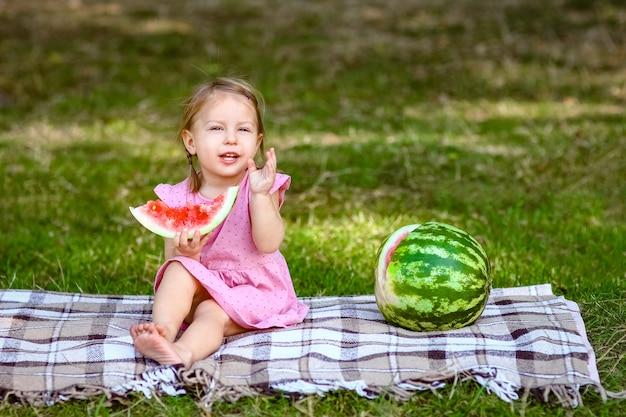 Bambino felice con anguria in natura