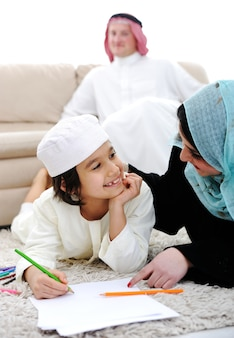 Bambino felice che lavora sui compiti a casa con la sua famiglia