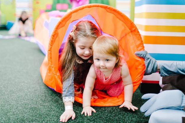 Bambini felici bambine che corrono nel tunnel e giocano con i giocattoli nella stanza dei giochi per bambini