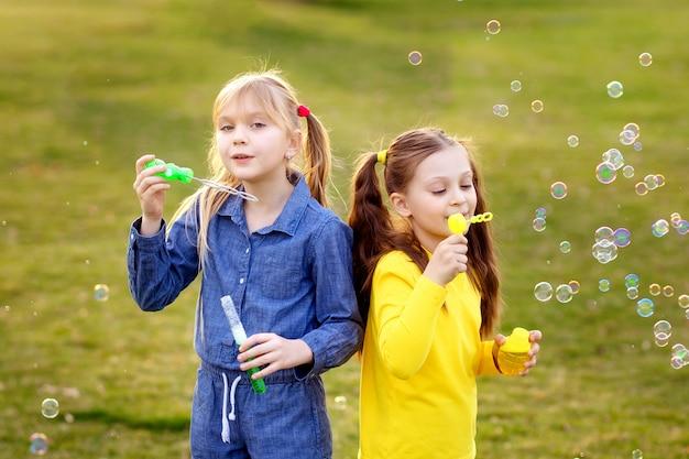 I bambini felici soffiano bolle di sapone nel parco estivo.