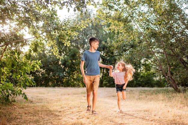 I bambini felici ragazzo e ragazza giocano rumorosamente nel parco. il fratello maggiore gioca con sua sorella in natura sotto i raggi del tramonto di una giornata estiva.