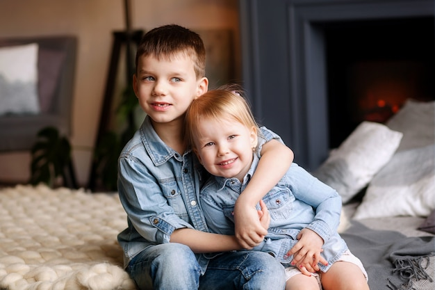 Bambini felici fratello e sorella si siedono e si abbracciano