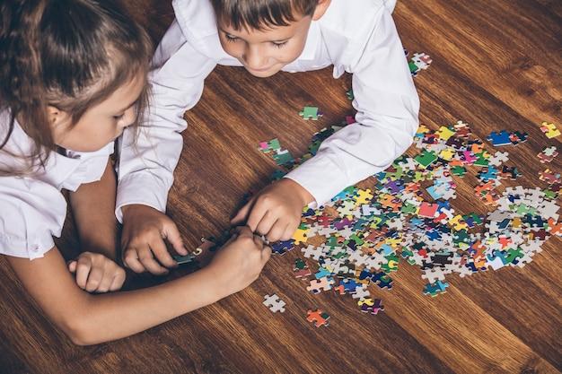 I bambini felici raccolgono puzzle sdraiato sul primo piano del pavimento