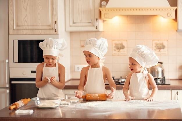 Bambini felici cuochi in cucina che cuociono i biscotti