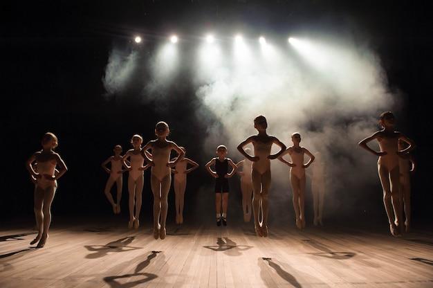 Bambini felici che fanno il salto di balletto su una scena illuminata scura.
